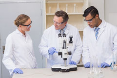 Concentrated scientists working together with microscope Stock Images