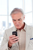 Concentrated senior businessman sending a text Royalty Free Stock Images