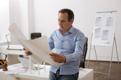 Concentrated senior engineer holding blueprint Royalty Free Stock Image