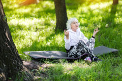 Concentrated senior lady having relaxation time in forest Royalty Free Stock Photo