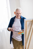 Concentrated senior man drawing picture in art workshop. Portrait of concentrated senior man drawing picture in art workshop Royalty Free Stock Photo
