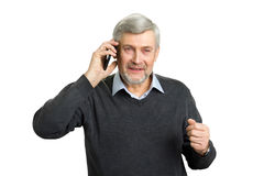 Concentrated senior man with phone. Mature man in office wear talking on smartphone and thinking. Elderly pensive man with mobile phone on white background Stock Image