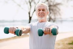 Concentrated senior man working out in park Stock Photo