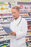 Concentrated senior pharmacist using tablet Stock Photo