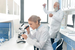 Concentrated senior scientists in uniform looking at flask while his colleague working with microscope on foreground Stock Image