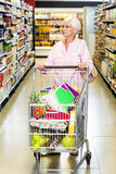 Concentrated senior woman pushing trolley Royalty Free Stock Photos