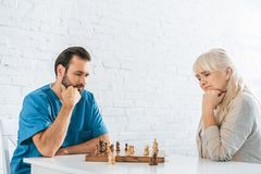 Concentrated senior woman and young social worker playing. Chess together royalty free stock photos