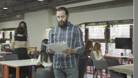 Concentrated serious bearded man studying papers documents standing in the modern office. Two women talking in the stock footage