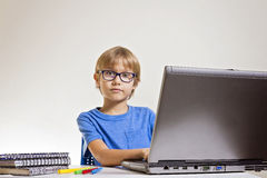 Concentrated serious boy with glasses using laptop computer while sitting on desk at home. Technology, education concept Royalty Free Stock Photography
