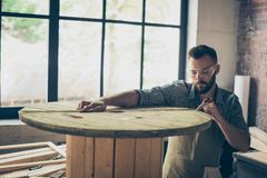 Concentrated serious handsome bearded talented skilled professional carpenter is measuring a wooden coil using tape-measure stock images