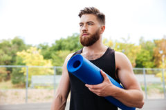 Concentrated serious male yoga instructor holding mat Royalty Free Stock Photography