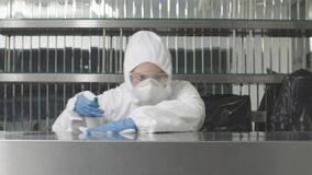 Concentrated serious woman in antiviral suit and respirator spraying sanitizer in gym and cleaning surface. Caucasian
