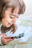 Concentrated seven year old girl examining the map with a loupe Stock Photography