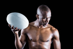 Concentrated shirtless sportsman holding rugby ball Stock Images