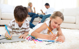 Concentrated siblings drawing lying on the floor Stock Photo
