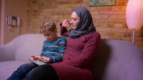Concentrated small boy playing game on tablet and his muslim mother in hijab caressing him tenderly at home. stock video