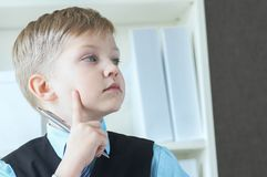 Concentrated small boy in suit thinking about money and budget increasing ways. Little financial director. stock photos