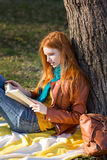 Concentrated smart girl reading a book under the tree Stock Photos