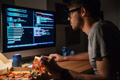 Concentrated software developer eating pizza and coding Royalty Free Stock Photos
