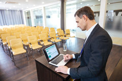 Concentrated speaker standing at tribune and using laptop. Concentrated speaker in black suit standing at the tribune and using laptop in empty meeting hall Royalty Free Stock Photos