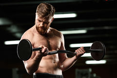 Concentrated sports man make sport exercises with barbell Royalty Free Stock Image