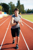 Concentrated sports man running down stadium track with earphones Stock Photography
