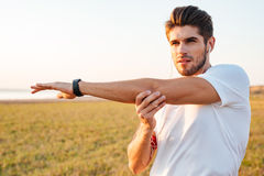 Concentrated sportsman stretching hands and listening to music with earphones Royalty Free Stock Photography