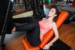 Concentrated sportswoman doing exercises for legs using gym equipment Royalty Free Stock Image