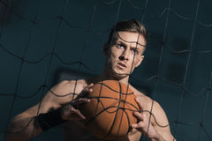 Concentrated sporty man holding basketball ball in hands Royalty Free Stock Photography