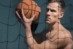 Concentrated sporty man holding basketball ball in hands Royalty Free Stock Image