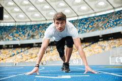 Concentrated sprinter getting ready to start a race. At the stadium stock photography
