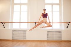 Ballerina doing elegant pull-up on barre. Concentrated strong beautiful young ballerina in pointe shoes doing elegant pull-up on barre in ballet classroom stock photo