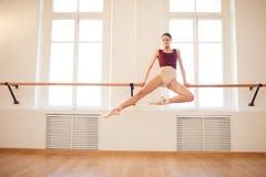 Ballerina doing elegant pull-up on barre stock photo