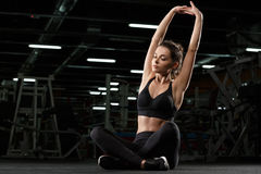 Concentrated strong fitness lady make sport stretching exercise Stock Images