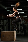 Concentrated strong sports lady make sport exercises jumping Stock Images
