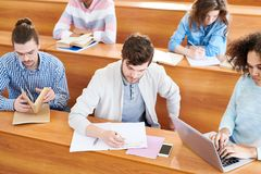 Concentrated students doing task at class royalty free stock photos