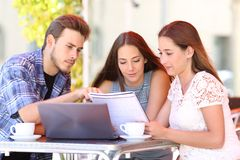 Concentrated students studying in a coffee shop royalty free stock photography