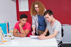 Concentrated students working with tablet together Stock Photos
