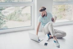 Concentrated stylish red  bearded man is sitting on the floor at Stock Photos