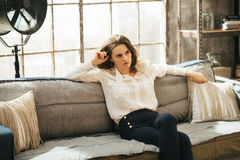 Concentrated stylish woman is sitting on couch in loft room Royalty Free Stock Photography