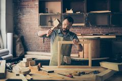 Concentrated successful knowledgeable smart bearded craftsman we. Aring checkered shirt apron and safety goggles is repairing a wooden frame for photo and royalty free stock images