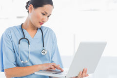 Concentrated surgeon using a laptop in hospital Royalty Free Stock Photography