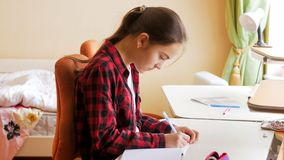 Portrait of concentrated girl doing homework in bedroom. Concentrated teen girl doing homework in bedroom royalty free stock photo