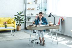 Concentrated teenage girl sitting at desk and studying. At home royalty free stock photo