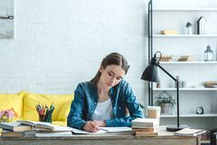 Concentrated teenage girl writing and studying at desk. At home royalty free stock photos
