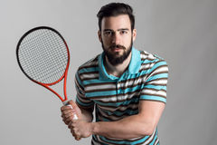 Concentrated tennis player in polo shirt holding racket Stock Image