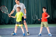 Concentrated tennis player teaching kids on court Stock Photography