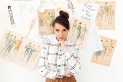 Concentrated thinking woman fashion illustrator. Picture of young concentrated thinking woman fashion illustrator standing near a lot of illustrations. Looking Stock Photography