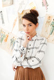 Concentrated thinking woman fashion illustrator. Picture of young concentrated thinking woman fashion illustrator standing near a lot of illustrations. Looking Royalty Free Stock Photo