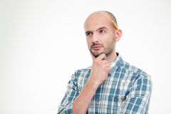 Concentrated thoughtful man in checkered shirt with pencil behind ear Royalty Free Stock Photos